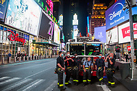 NEW YORK, NY - MAY 27: A group of firefighters wearing face masks wait alongside the Billboards in Times Square on May 27, 2020 in New York City. Some Times Square billboards went off for a minute in gratitude to the millions of medical workers and essential workers who have given their lives to fight the COVID-19 pandemic. The number of deaths from this pandemic exceeded 100,000 in the United States. (Photo by Pablo Monsalve / VIEWpress via Getty Images)