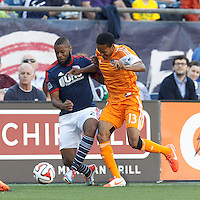 New England Revolution defender Andrew Farrell (2) attempts to control the ball as Houston Dynamo midfielder Ricardo Clark (13) pressures. In a Major League Soccer (MLS) match, the New England Revolution (blue/white) defeated Houston Dynamo (orange), 2-0, at Gillette Stadium on April 12, 2014.