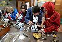 NWA Democrat-Gazette/ANDY SHUPE<br /> Sim Barrow (center), environmental science coordinator for Fayetteville Public Schools, helps set up dissecting microscopes Wednesday, Nov. 6, 2019, for Ayden Bryan, 8 (from left); Kieomi Tarkwon, 8; and Calvin Clancy, 9; all third-graders in Tina Moretz's class at Leverett Elementary School, during a lesson about fossils at the Kessler Mountain Outdoor Classroom and Nature Center operated by the Northwest Arkansas Land Trust in Fayetteville. Students learned about fossils in small groups in the classroom and outside on the trails around Kessler Mountain.