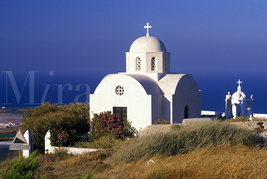 A chapel in the countryside overlooks the blue Mediterranean Sea. Santorini, Greece.