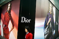 A woman walks past a billboard for Christian Dior fashion on the side of the Deji Plaza shopping mall in the central Xinjeikou shopping area of Nanjing, Jiangsu, China.