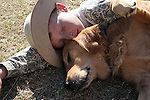 A young red head freckled country boy laying down on the ground resting with his golden retriever dog