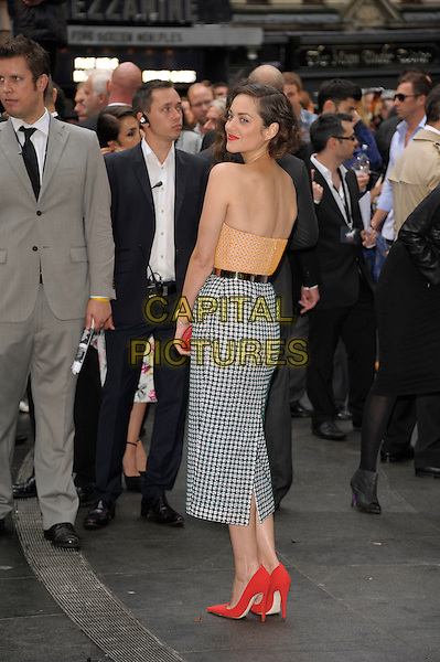 Marion Cotillard (in Christian Dior Couture).'The Dark Knight Rises' European premiere at Odeon Leicester Square cinema, London, England..18th July 2012.full length orange strapless top looking over shoulder back behind rear gold metal waistband white black pattern skirt red clutch bag shoes.CAP/PL.©Phil Loftus/Capital Pictures.