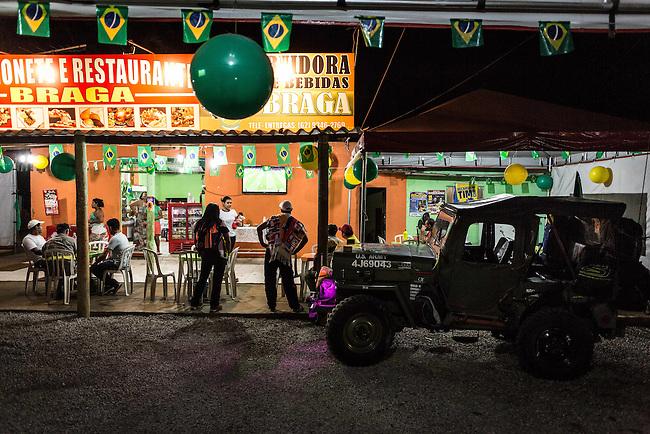 Cae la noche en la carretera y  tripulantes del Willis 1953 de   John Jairo Zapata  se detenien para ver un partido en un peque&ntilde;o restaurante en el camino de Braislia a  Cuiaba,  el  20 Junio 2014. <br /> John Jairo es revendedor de carros y se enamor&oacute; del Willis pertenecia antiguamente al ejercito  de EEUU ni bien lo vi&oacute; y lo reconstruy&oacute; totalmente. A lo largo de dos meses cumple su sue&ntilde;o de acompa&ntilde;ar a la Seleccion Colombia en el mundial de Brasil, viajando miles de kilometros a una marcha promedio de 60 KM por hora, durmiendo en alojamientos economicos y compartiendo gastos con eventuales hinchas que se han ido sumando a la Expedicion Jipao, como el la ha bautizado.<br /> <br />   Lorenzo Moscia/Archivolatino<br /> <br /> lCOPYRIGHT: Archivolatino<br /> Solo para uso editorial, prohibida su venta y su uso comercial