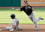 """Reno's shortstop Jake Elmore turns a double play as the Aces are transformed into the Reno Ghost Riders for the """"What Could Have Been Weekend"""" series against the Salt Lake Bees on Thursday night July 12, 2012 at Aces Ballpark in Reno, NV."""