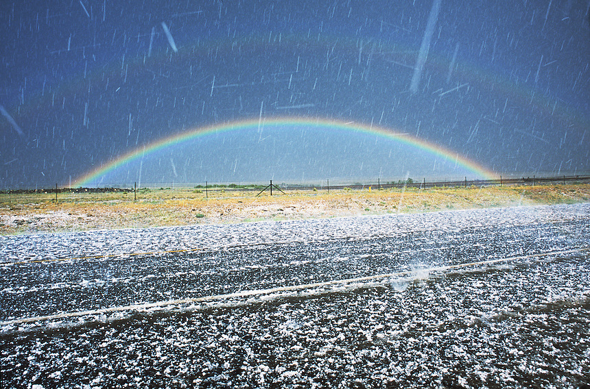 Display of full primary and secondary rainbows while hailstorm is in progress along highway in the highlands of northeastern New Mexico.
