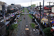 Children walk on the railway line in an crowded area around the North Cemetery in Manila, Philippines. Photo: Sanjit Das