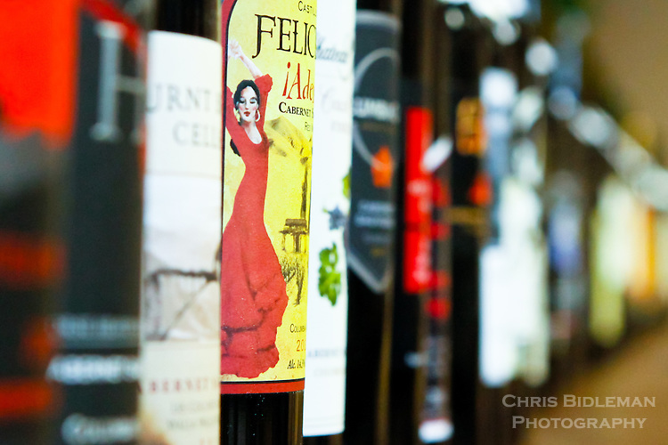A row of cabernet savignon bottles are lined up with the focus on a label is a dancer in a red dress with a shallow field of focus down the row of bottles.  Taken during the Savor NW 2014 Judging, Cannon Beach, OR