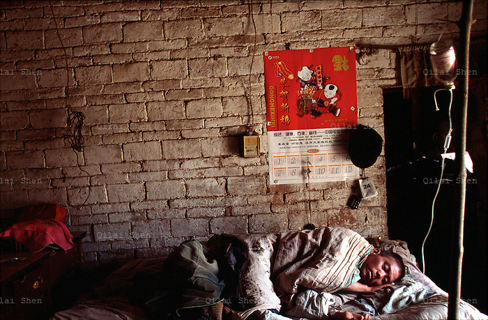QSFeature04AIDS008 20020504 DONGGUAN, CHINA: .AIDS patient Yu Da Guan receives an IV drip, the only means of treatment against a high fever, while laying on his sick bed at his home in Dongguan village, Henan Province, China 04 May 2002. He died 2 weeks after this picture was taken. Over 700,000 peasant farmers in Henan Province have contracted the HIV virus when they participated in the unregulated blood selling/buying boom of the early and mid nineties..Photo by: Qilai Shen