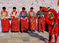 Asia, Buthan, Paro Dzong, Tshechu festival,  clown jokeing with young girls dressed for ceremony