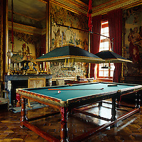 Large, shaded pendant lights hang over the billiard table in a room decorated with tapestries