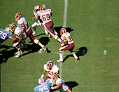 Washington Redskins running back Keith Griffin (35) carries the ball during the game against the Houston Oilers at RFK Stadium in Washington, DC on September 16, 1985.  Blocking for Griffin are: Redskins offensive guard R.C. Thieleman (69), left tackle Joe Jacoby (66), right tackle Mark May (73), right guard Ken Huff (61), and center Rick Donnalley (76).  Defending for the Oilers are: left defensive end Ray Childress (79) and right defensive end Jesse Baker (75).  The Redskins won the game 16 - 13.<br /> Credit: Howard L. Sachs / CNP