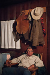 Night time in the cabin during the fall cattle gathering in the High Sierra...Roger Lopes relaxes in a chair after a hard day of gathering cattle