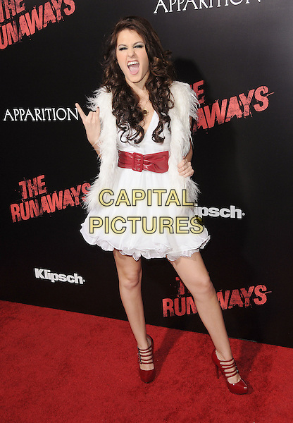 """SCOUT-TAYLOR COMPTON .at the L.A. Film Premiere of """"The Runaways"""" held at The Arclight Cinerama Dome in Hollywood, California, USA, March 11th 2010.                                                                    .arrivals full length white dress red waist belt hand rock gesture mouth open funny  fur fluffy gilet sleeveless strappy mary janes shoes paltform .CAP/RKE/DVS.©DVS/RockinExposures/Capital Pictures"""