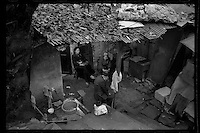 Residents sit outside their house in Shibati slum area of Chongqing, China's southwestern municipality, in April, 2011.