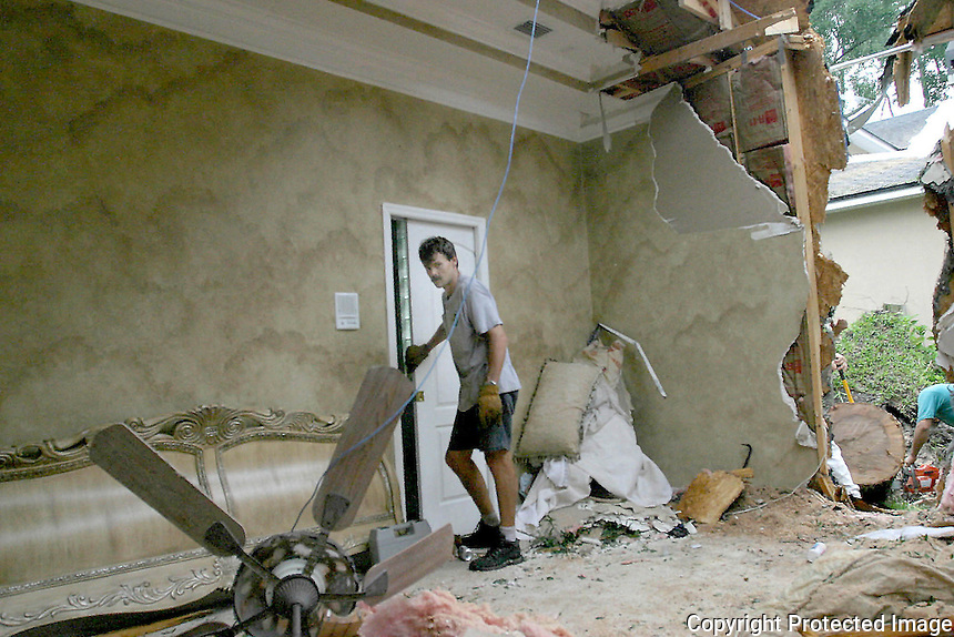 9/08/04...Gary Wilcox/staff..... This house on Tallwood Road   in Jacksonville Beach had a tree go through the bedroom during Hurracane Frances late  Sunday night. M.K. Wakefield shows the bathroom where he was in when the tree came through his bedroom.
