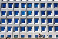 Woman pushing man in wheelchair walking along Larsens Plads in Copenhagen, Denmark.