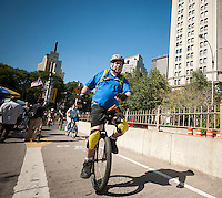 Unicyclists of all skill levels, ages and gender ride across the Brooklyn Bridge for their 13-mile trip to Coney Island on Friday, August 29, 2014 as part of the NYC Unicycle Festival. The convergence of unicyclists was the start of the 3-day Fifth Annual New York City Unicycle Festival which besides the ride, features performances, classes and just plain fun with events happening on Governor's Island. (© Richard B. Levine)