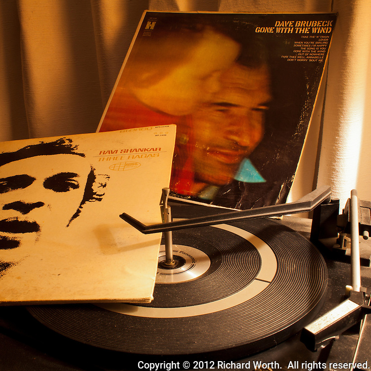 In December 2012, Dave Brubeck and Ravi Shankar died a week apart.  In this image, 1960s vintage albums rest on a dusty turntable of about that same era - the age of LPs at 33 and a third, and a couple of the giants who strode through.