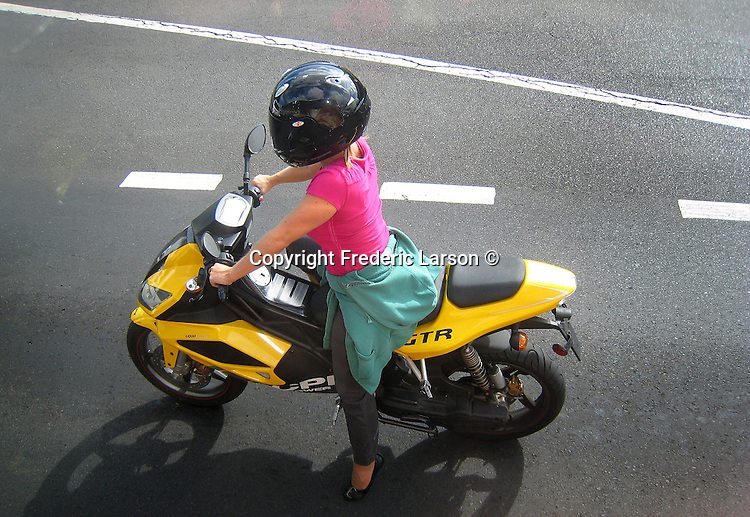 A woman has style while riding her motorcycle on the Streets of Honolulu, Hawaii on the island of Oahu.