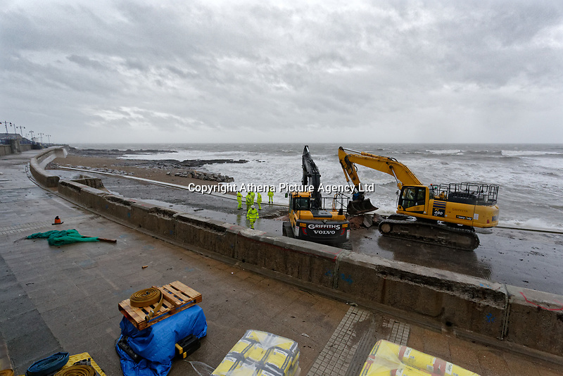 Pictured: Workers and heavy machinery work on the promenade in Porthcawl, Wales, UK. Friday 12 October 2018<br /> Re: Strong winds and rain caused by Storm Callum in south Wales, UK.