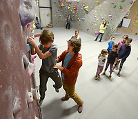 NWA Democrat-Gazette/ANDY SHUPE<br /> Jason Groves (center), co-owner of Ozark Climbing Gym in Springdale, lends a hand Friday, Jan. 4, 2018, as Santiago Machado, 8, of Fayetteville works on his footwork during a three-day Winter Climbing Camp at the gym in Springdale. Campers learned about climbing equipment, holds, routes and proper climbing and safety techniques.