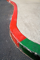 Fine art city abstract of curving curb, green in foreground, changing to red for remainder of curb, with dark gray asphalt on left and very light concrete sidewalk on right.