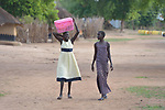 Two young women walk through the Rhino Refugee Camp in northern Uganda. As of April 2017, the camp held almost 87,000 refugees from South Sudan, and more people were arriving daily. About 1.8 million people have fled South Sudan since civil war broke out there at the end of 2013. About 900,000 have sought refuge in Uganda.