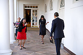 United States President Barack Obama watches as First Lady Michelle Obama playfully greets him on the Colonnade of the White House, February 12, 2013. Tina Tchen, Chief of Staff to the First Lady, and Personal Aide Kristin Jones, left, accompany Mrs. Obama. .Mandatory Credit: Pete Souza - White House via CNP