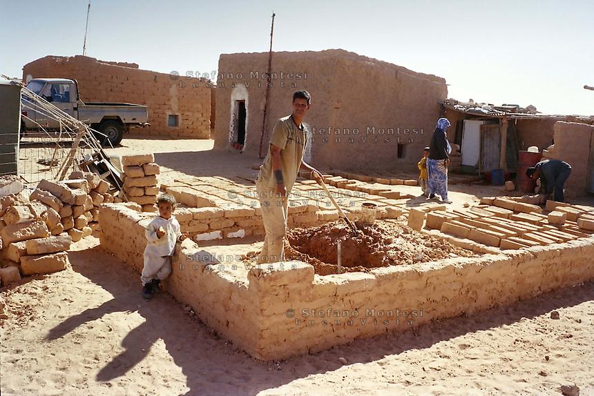 Gennaio 2005.Campo Profughi Saharawi di Smara.Un uomo costruisce la casa  con i mattoni di  sabbia.January 2005.Saharawi refugee camp of Smara.A man builds a house with bricks made of sand..