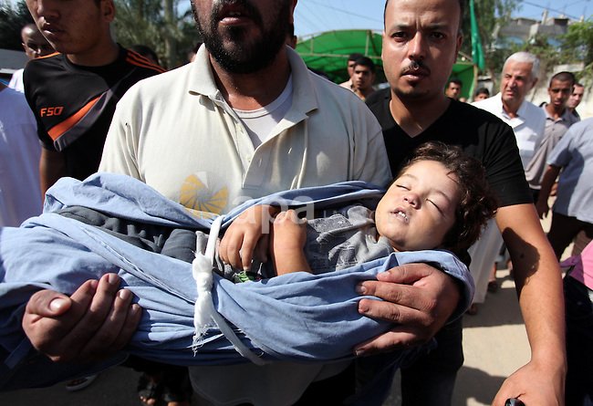 """Relatives of two-year-old Palestinian girl Rahaf, mourn during the funeral of the toddler and her pregnant mother on October 11, 2015, at the al-Nusairat refugee camp, in central Gaza Strip. A pregnant Palestinian mother and her toddler daughter were killed in the air strike in the Zeitun sector south of Gaza City while three others were still trapped under the ruins of a house, medical sources said. Israel said it had targeted """"two Hamas weapon manufacturing facilities"""" in response to two rocket launches at Israel the day before. Photo by Ashraf Amra"""