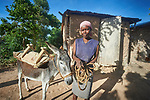 Rose Marie Pierre poses with her donkey in Picmy, a village on the Haitian island of La Gonave where Service Chrétien d'Haïti is working with survivors of Hurricane Matthew, which struck the region in 2016. SCH, a member of the ACT Alliance, supports agriculture on the island by providing tools, seeds, and technical support and training for farmers. It also provided donkeys to many families. In Pierre's case, the donkey helps her bring water from a long distance to her family.