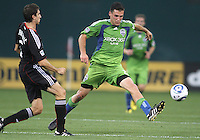 Dejan Jakovic #5 of D.C. United slips the ball past Leonardo Gonzalez #19 of Seattle Sounders FC during an MLS match at RFK Stadium on July 15 2010, in Washington DC.Seattle won 1-0.