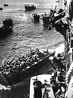 U.S. troops go over the side of a Coast Guard manned combat transport to enter the landing barges at Empress Augusta Bay, Bougainville, as the invasion gets under way.  November 1943. (Coast Guard)<br /> Exact Date Shot Unknown<br /> NARA FILE #:  026-G-3183<br /> WAR &amp; CONFLICT BOOK #:  1164