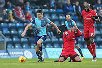 Luke O'Nien of Wycombe Wanderers comes away with the ball only to be judged that he fouled Paul McCallum of Leyton Orient (2nd right) during the Sky Bet League 2 match between Wycombe Wanderers and Leyton Orient at Adams Park, High Wycombe, England on 17 December 2016. Photo by David Horn / PRiME Media Images.