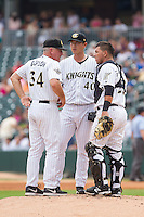 Charlotte Knights pitching coach Richard Dotson (34) has a meeting on the mound with starting pitcher Chien-Ming Wang (40) and catcher Miguel Gonzalez (23) during the game against the Pawtucket Red Sox at BB&T Ballpark on August 8, 2014 in Charlotte, North Carolina.  The Red Sox defeated the Knights  11-8.  (Brian Westerholt/Four Seam Images)