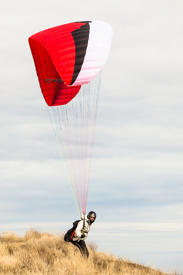 One adult male paraglider prepares to lift off the side of Steptoe Butte State Park in Eastern Washington State.