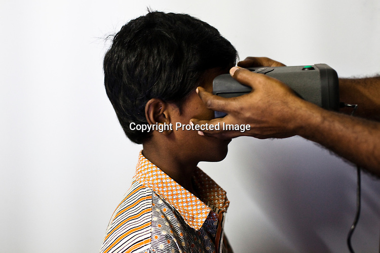 A young boy looks inside the iris scanner as part of the enrollment that is on its way in Naagaaram village, outskirts of Hyderabad in Andhra Pradesh, India. India is assigning each one of its 1.2 billion people a unique ID number based on digital finger prints and iris scan. Photograph: Sanjit Das/Panos