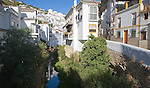 River running past whitewashed houses Setenil de las Bodegas, Cadiz province, Spain