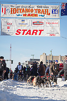 John Baker and team leave the ceremonial start line at 4th Avenue and D street in downtown Anchorage during the 2014 Iditarod race.<br /> Photo by Jim R. Kohl/IditarodPhotos.com