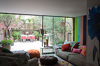 The glazed extension designed by architects Hiscox Parlade, looks out onto a contemporary courtyard garden complete with faux, pink blossomed tree