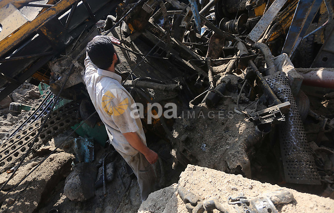 A Palestinian man looks at the damage following an Israeli air strike on a workshop in Gaza City on July 2, 2016. Israeli air strikes hit four sites in the Gaza Strip, causing damage but no injuries, officials said, after Palestinian militants fired a rocket that struck a building in southern Israel. Photo by Mohammed Asad