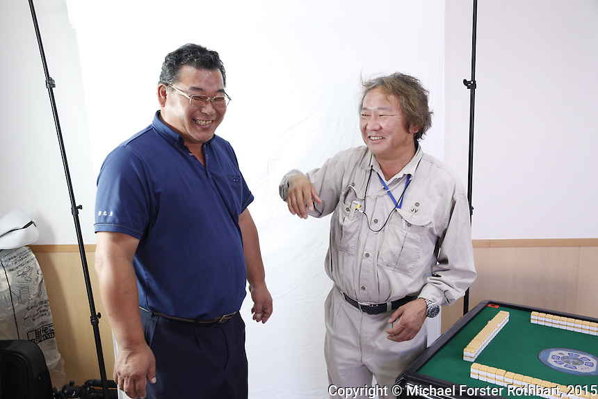 Civil engineer Kenichi Hayashi is one of 15,800 evacuees from Tomioka, a town in the Fukushima exclusion zone. He is also a decontamination supervisor working for Maruto, a construction company cleaning up Tomioka. He poses for a portrait with his friend Ben Takeda, another decontamination supervisor, beside the mahjong table in his Maruto office. Full caption to come.<br /> <br /> &copy; Michael Forster Rothbart Photography<br /> www.mfrphoto.com &bull; 607-267-4893<br /> 34 Spruce St, Oneonta, NY 13820<br /> 86 Three Mile Pond Rd, Vassalboro, ME 04989<br /> info@mfrphoto.com<br /> Photo by: Michael Forster Rothbart<br /> Date:  10/13/2015<br /> File#:  Canon &mdash; Canon EOS 5D Mark III digital camera frame A20642