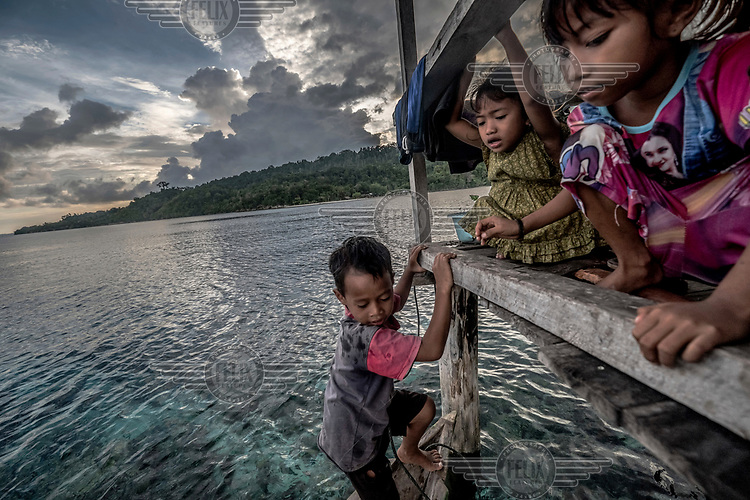 Bajau children play on the porch of their home in the stilt village of Pulo Papan.