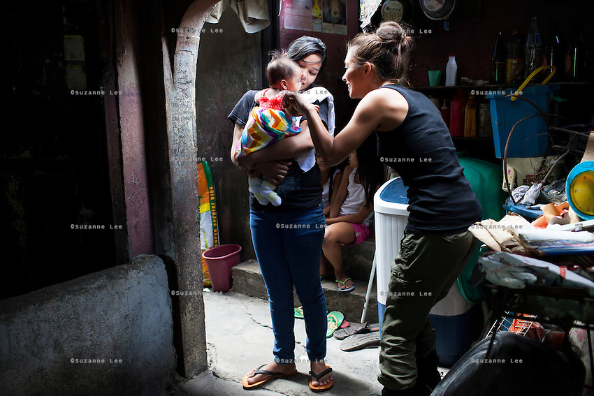 Myleene Klass, a celebrity from the UK, meets single mother Josephine Savares, 18, as she holds her 1st child Jihan, aged 4 months, outside her family house where she lives with her father, in Paranaque, Metro Manila, The Philippines on 19 January 2013. Josephine had decided to feed her baby formula during her pregnancy and had no idea that her father had to pay such a high price for it. Her family goes without food some days, and her siblings have had to stop school in order to afford the formula. Photo by Suzanne Lee for Save the Children UK