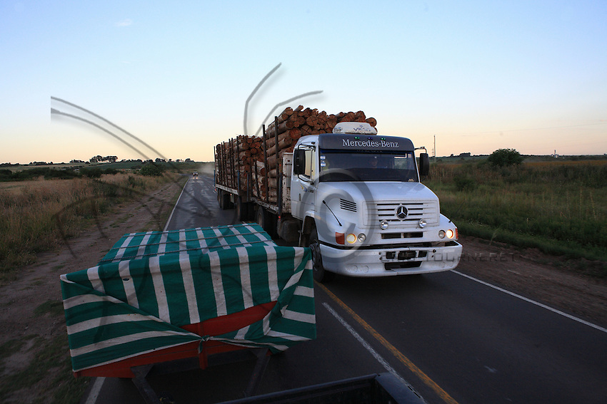 A truck loaded with wood passes Carlos trailer full of hives. It's coming back from the North where the rapid spread of soy crops engenders the destruction of the primal forest.