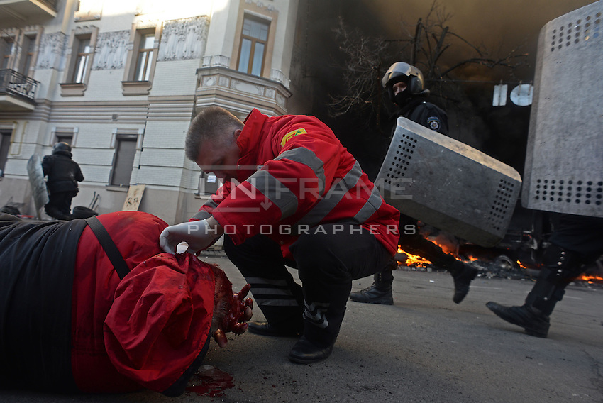 A Red Cross Medic help a man that has been shot and is heavily bleeding in the  battlefield of maidan square.  Kiev, Ukraine
