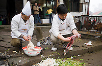 Chinese chefs gut rabbit and pluck chicken to cook for restaurant customers at Bao Ding near Chongqing, China