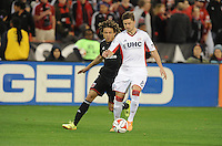Washington, D.C.- March 29, 2014. Chris Tierney (8) of the New England Revolution shields the ball against Nick DeLeon (14) of D.C. United.  D.C. United defeated the New England Revolution 2-0 during a Major League Soccer Match for the 2014 season at RFK Stadium.