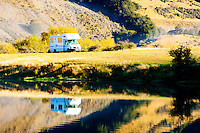 Caravan Parked at an Autumnal Lake Moke DOC Campsite, Queenstown, South Island, New Zealand. Lake Moke, 10km from Queenstown is both a stunning lake and a department of conservation campsite (DOC campsite) with access for both caravans and campervans. In the early mornings Lake Moke is often perfectly still providing picture perfect reflections of the surrounding hills and mountains in the water. The combination of a fabulous golden hour as the sun rose over the hills, the morning mist lifting from the lake, and the rich, orange, autumn trees made this nights camping at the Lake Moke department of conservation campsite (DOC campsite) particularly special.